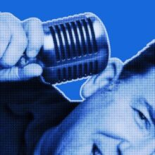 Blue-filtered partial portrait of man smiling and holding a microphone to his right ear