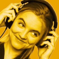 Yellow-filtered portrait of woman smiling looking to the side while wearing and holding headphones with both hands